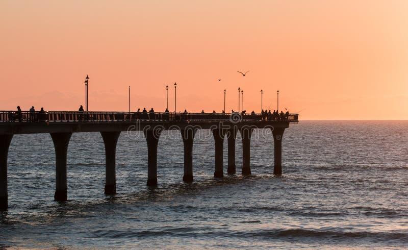 人们在码头钓鱼在日出 库存图片