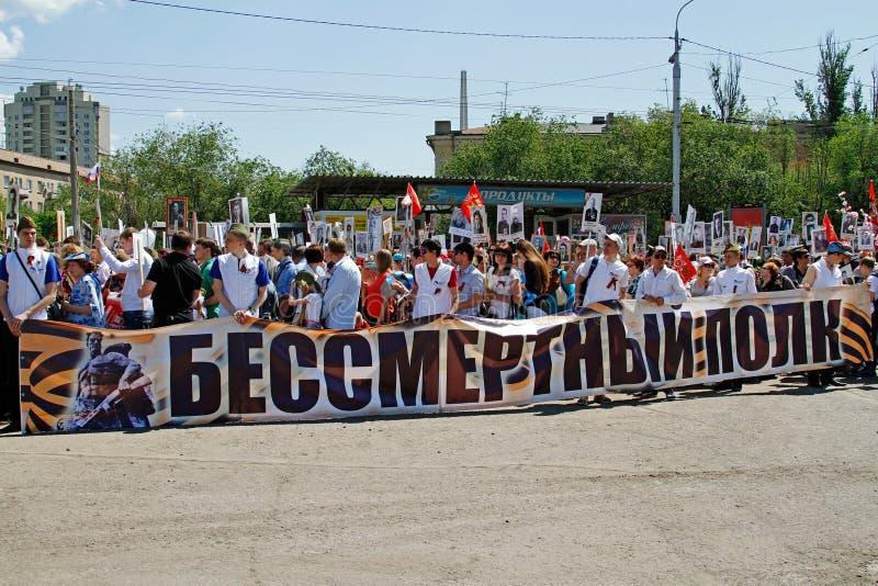 人们在胜利天拿着他们的亲戚不朽的军团和画象横幅在伏尔加格勒 库存图片