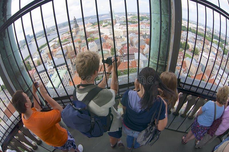 人们在里加,拉脱维亚拍从圣彼得高耸的照片 免版税库存照片