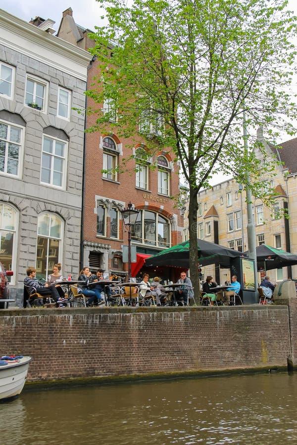 人们在阿姆斯特丹临近在运河江边的咖啡馆  免版税库存图片
