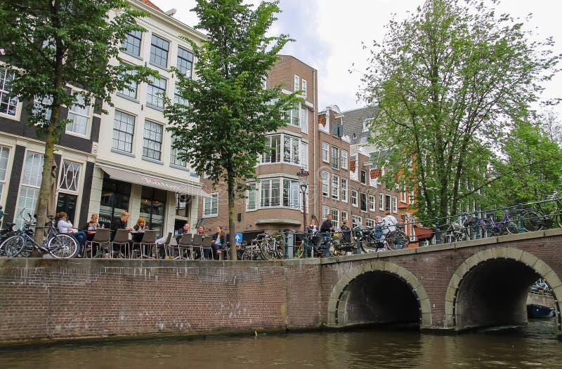 人们在阿姆斯特丹临近在运河江边的咖啡馆  免版税库存照片