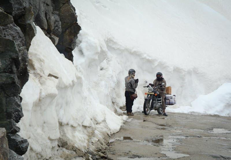 人们在雪路骑摩托车在Khardungla,印度 免版税库存照片