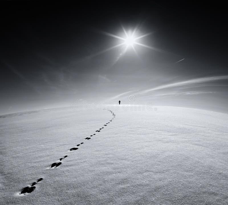 人 地球 宇宙 孤独的人走在雪在一个野兔的足迹的外壳领域的在太阳的背景的和飞行飞行 库存图片