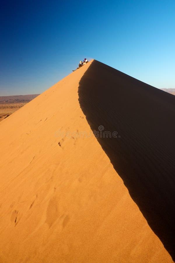 人们坐沙丘观看的日落 免版税库存照片