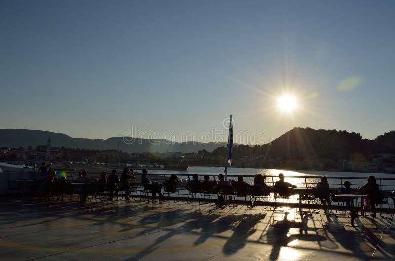 人们坐渡轮在日落 免版税库存图片