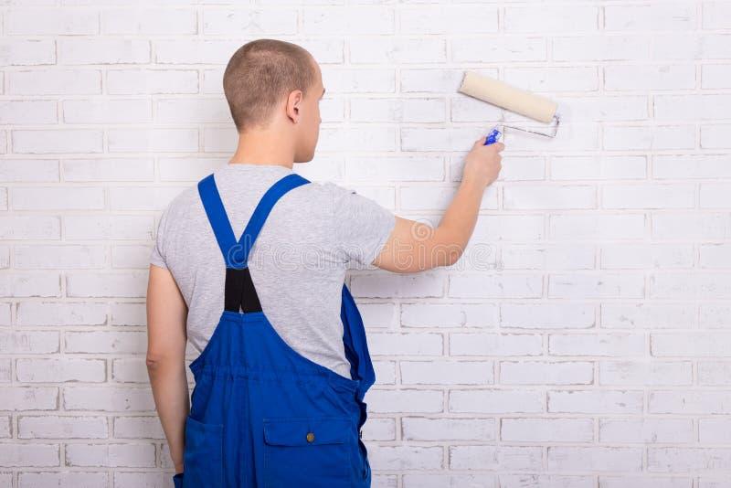 年轻人画家背面图工作服绘画砖墙的w 免版税库存图片