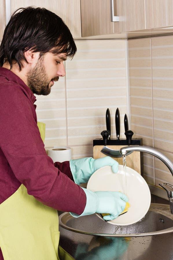 年轻人洗涤的盘 免版税库存照片