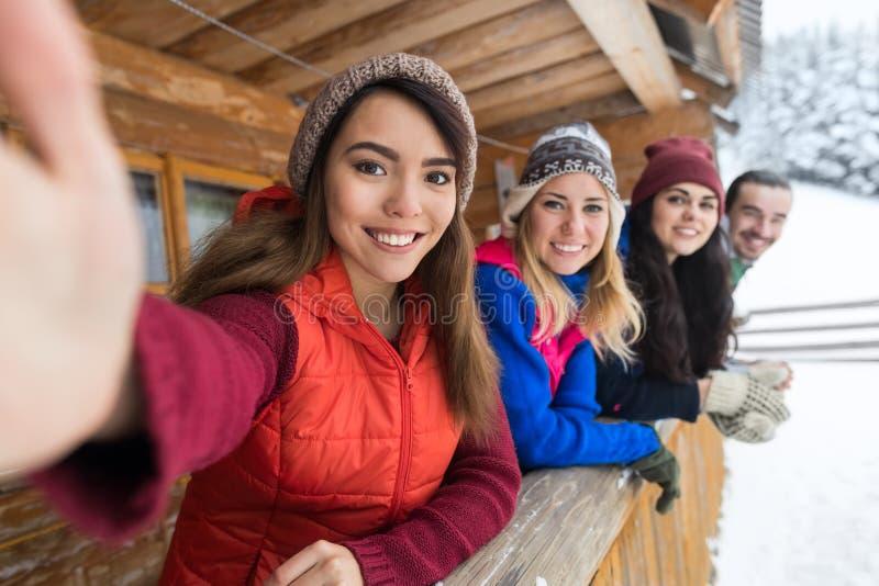人们编组采取Selfie照片巧妙的电话木乡间别墅大阳台冬天雪山区度假村 免版税库存图片