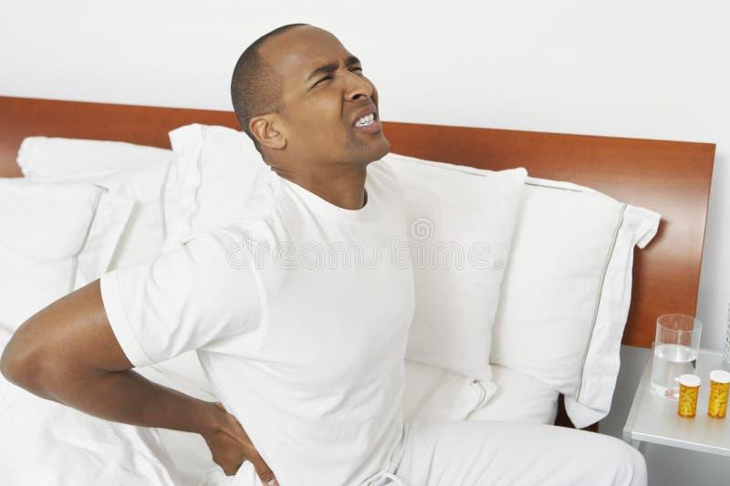 人以腰疼在床上 库存图片