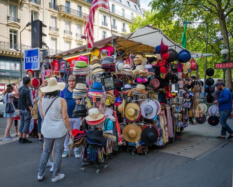 人们试穿帽子在一个纪念品摊在巴黎 免版税库存照片
