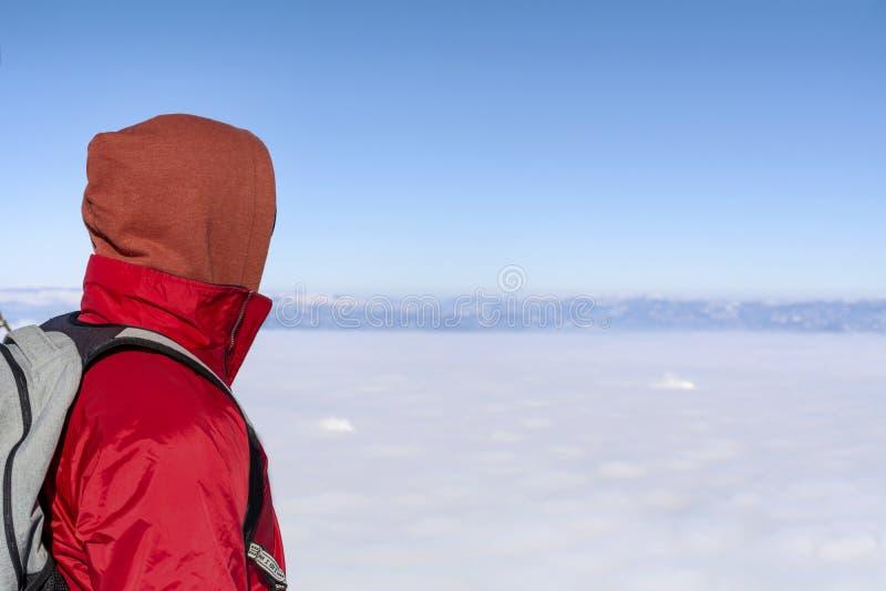 年轻人画象冬天山的在城市雾上 库存图片
