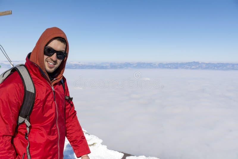 年轻人画象冬天山的在城市雾上 免版税图库摄影