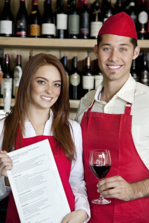 年轻人画象等待有酒杯的职员和在酒吧的菜单卡片 免版税库存照片
