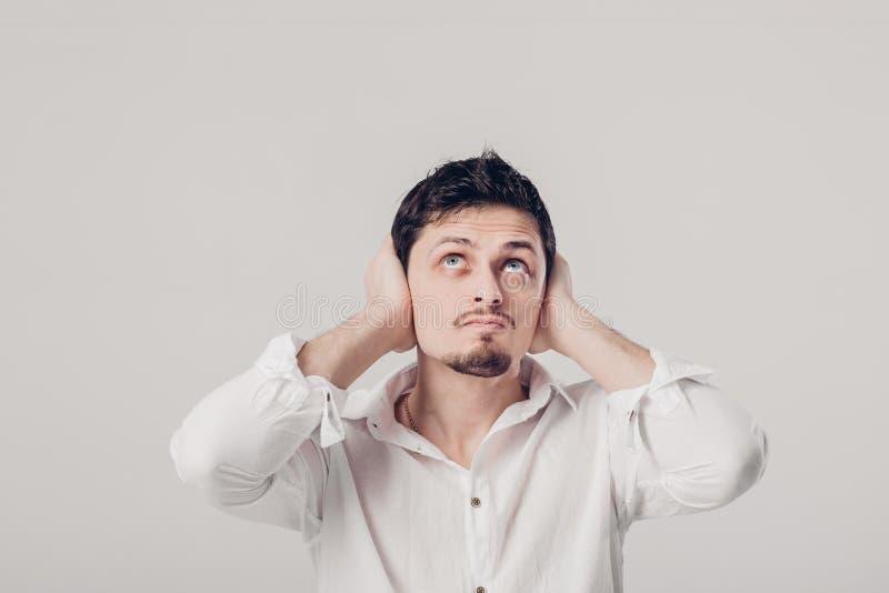 年轻人画象衬衣的用他的手ag盖他的耳朵 免版税库存照片