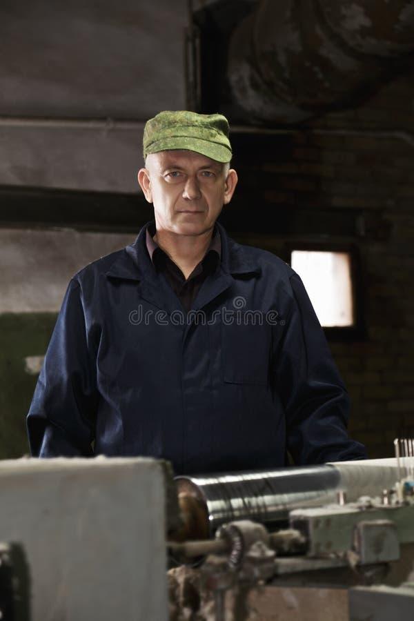 人画象绿色盖帽的在机器 免版税库存图片