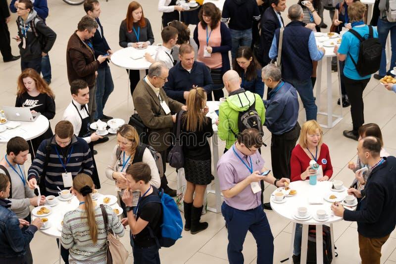 人们采取小圆面包用在咖啡休息的葡萄干在会议 免版税库存图片