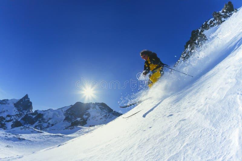 年轻人滑雪在山的粉末雪在冬天 库存照片