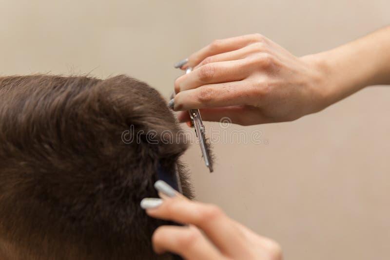 人` s发型和haircutting在理发店或发廊 库存图片