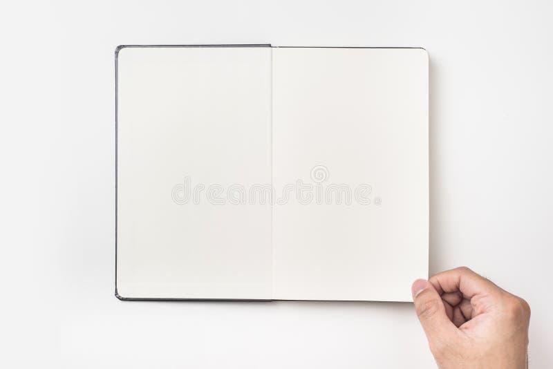人` s手举行黑色笔记本顶视图  图库摄影