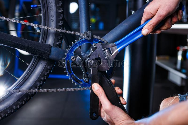 人` s手自行车机械工特写镜头在商店使用instment调整和修理自行车曲柄汇编 库存照片