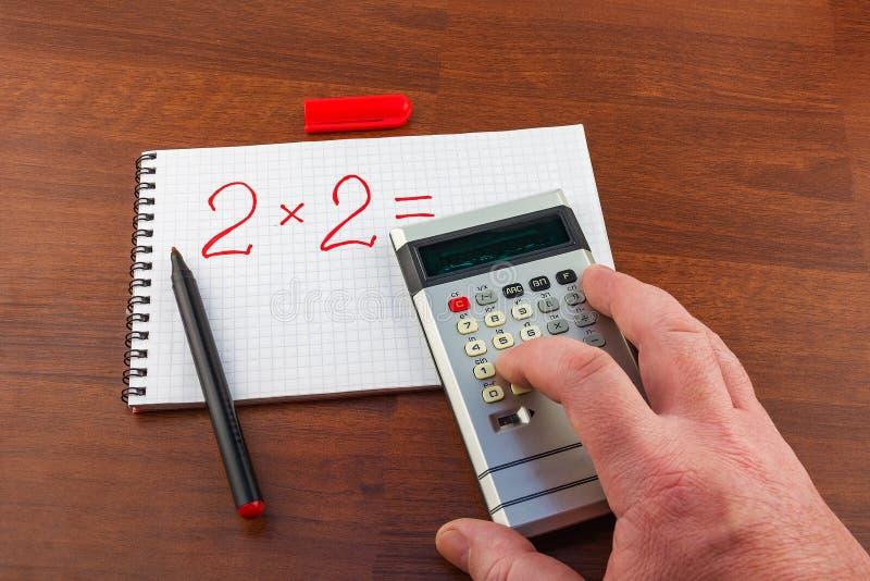 人` s手解决在笔记本板料写的等式在加州 免版税库存照片
