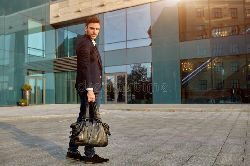 人` s时尚 在一套时髦衣服和一白色衬衫的一个年轻男性商人有一个大黑提包的来自时兴 免版税库存照片