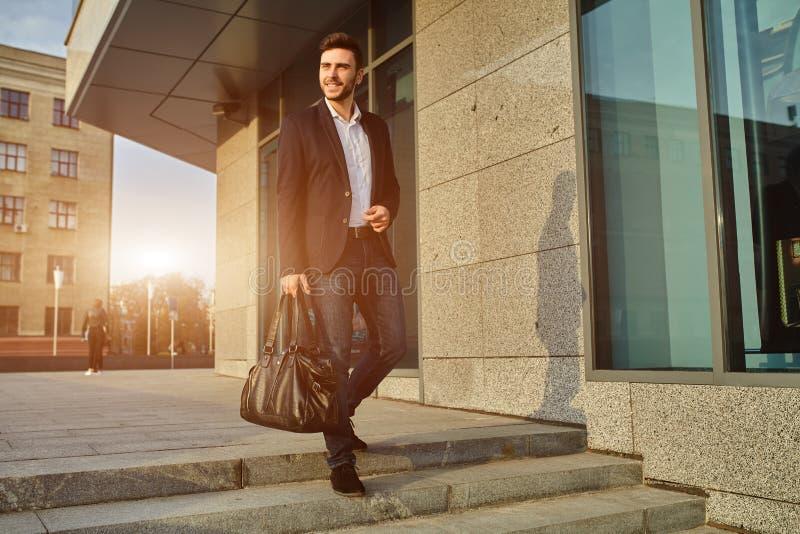 人` s时尚 在一套时髦衣服的一个年轻男性商人和有一个大黑提包的一白色衬衫 库存图片