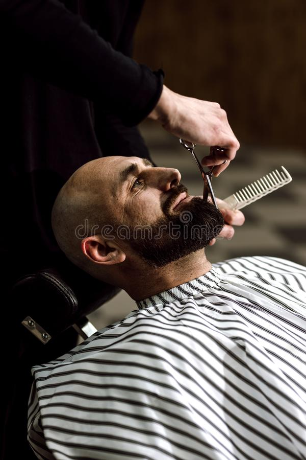 人` s时尚 理发师在时髦的理发店剪残酷人胡子  库存图片