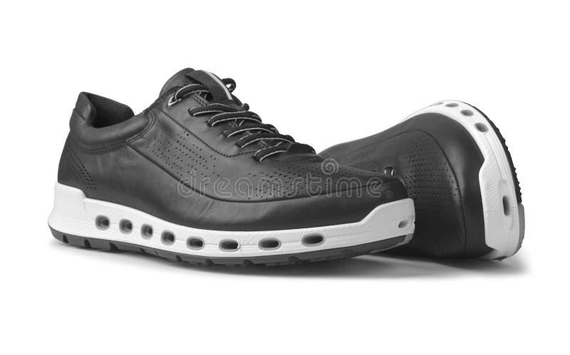 人` s炫耀在白色背景的鞋子 免版税库存照片