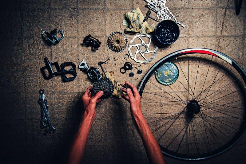 人` s胳膊修理自行车 没有任何商标,到处有备件 免版税库存图片