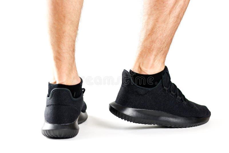 人` s黑色炫耀鞋子 对体育 隔绝在白色backgrou 库存图片