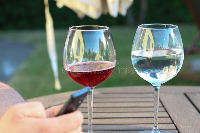 人smartphone使用 充分的玻璃半红葡萄酒 充分的玻璃半水 与人的饮用的挑选概念 图库摄影