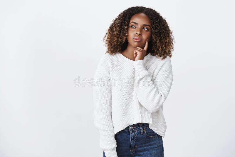 什么应该我预定 有卷发的体贴的可爱的年轻非裔美国人的妇女在毛线衣决定什么的 库存照片