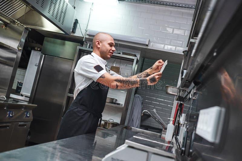 什么是下的 有纹身花刺的英俊的秃头男性厨师在他的看命令名单的胳膊在餐馆厨房里 免版税库存图片