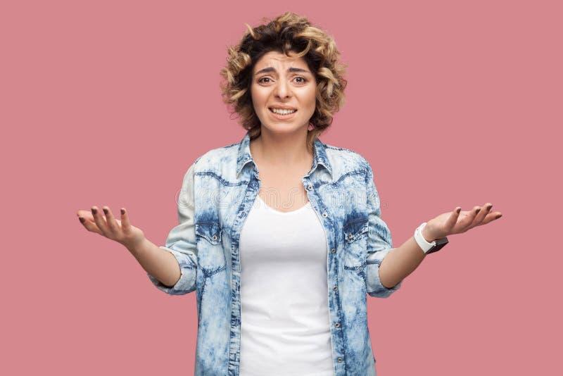 什么?迷茫或震惊年轻女人画象有卷曲发型的在与被举的胳膊和看的偶然蓝色衬衣身分 免版税库存图片