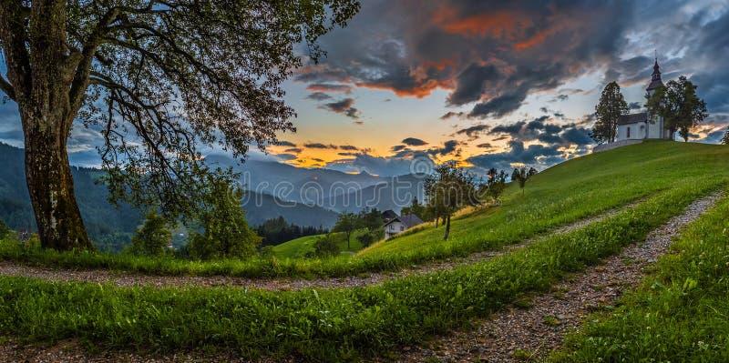 什科菲亚洛卡,斯洛文尼亚-斯洛文尼亚阿尔卑斯的美好的全景农村风景有Sveti Tomaz迷人的小山顶教会的  免版税图库摄影