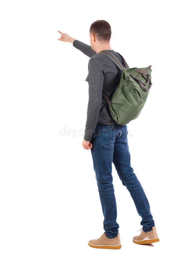 今后指向后面观点的有一个绿色背包的一个的人 库存照片