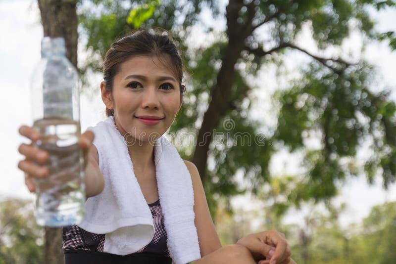今后给饮用水瓶的少妇佩带的体育穿戴 满身是汗的渴,休息时间 体育健康女孩 免版税图库摄影