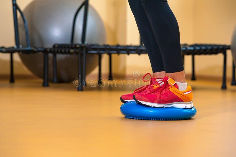 介入在健身房的体育女孩的腿 库存图片