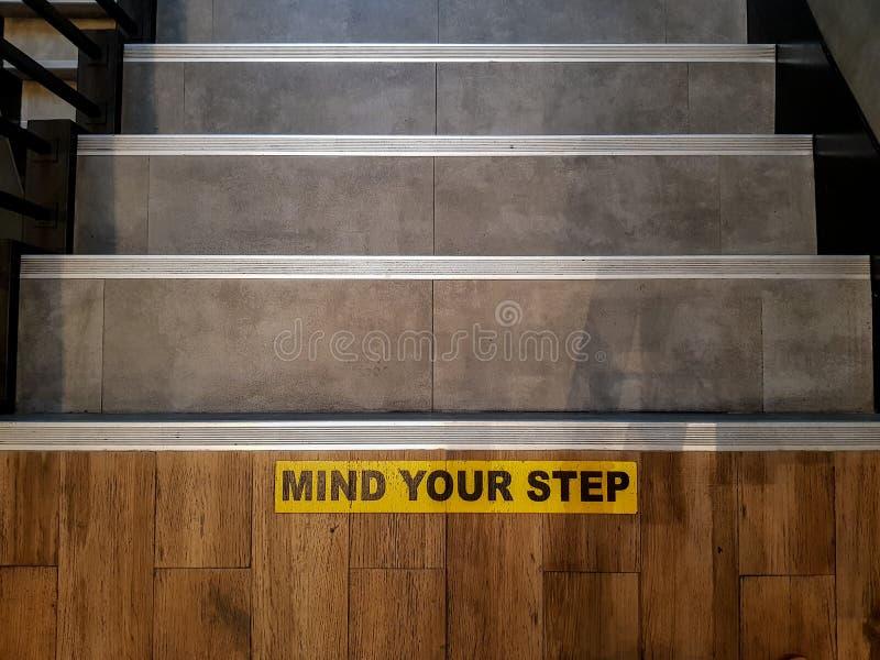 介意在楼梯的砖地打印的您的步标志 免版税库存照片