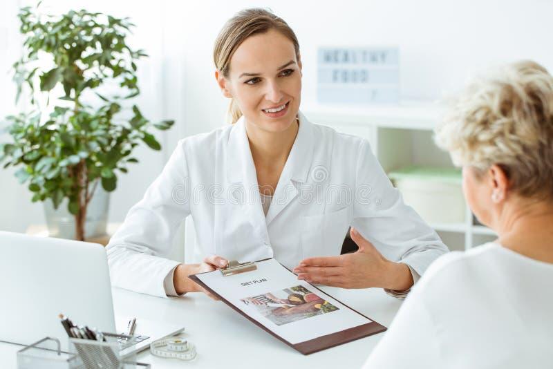 介绍健康饮食的女性医生 库存照片