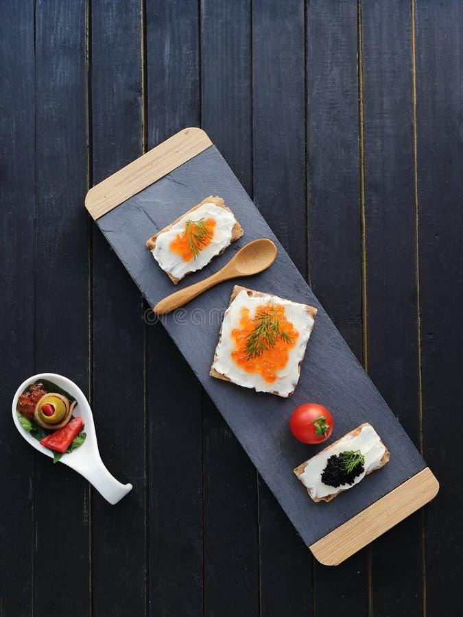 介绍委员会:绿橄榄填装了腌汁,包裹在花梢白色小板材,红色和黑鱼子酱的鲥鱼在油炸马铃薯片 免版税库存照片