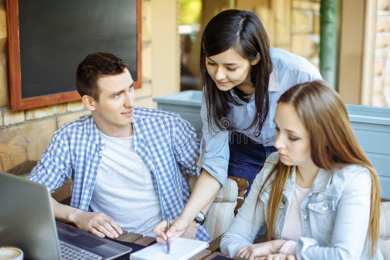 介绍新的企业项目的概念 小组年轻工友谈论想法互相在现代办公室 库存照片