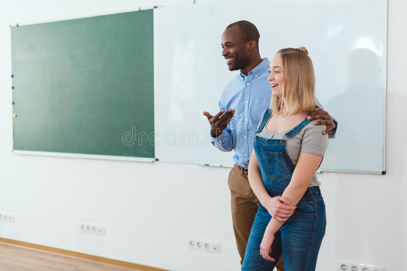 介绍新的女孩的微笑的非裔美国人的老师 免版税库存照片