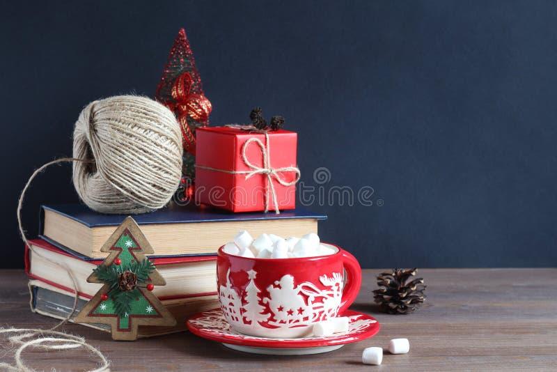 仍然圣诞节生活 圣诞节杯子用蛋白软糖,堆书和一件红色礼物 图库摄影