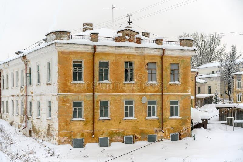仍然居住的老大厦在有被破坏的一楼的一老俄国小镇和底层人们居住的地方 免版税库存图片