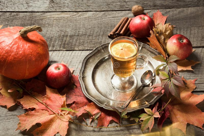 仍然秋天生活 茶与秋叶和南瓜装饰的在木板 库存图片