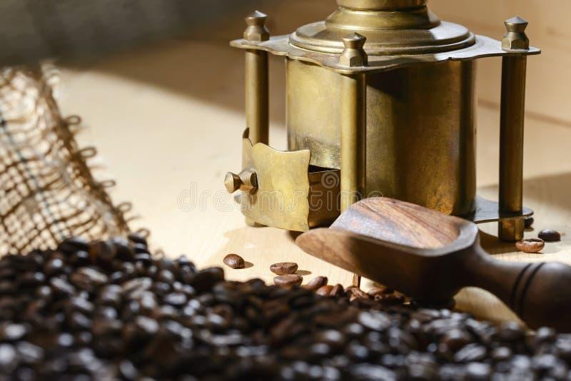 从一个咖啡袋在一个老铜磨咖啡器和小铲的看法从橄榄色的木头的大块产品的 免版税库存照片