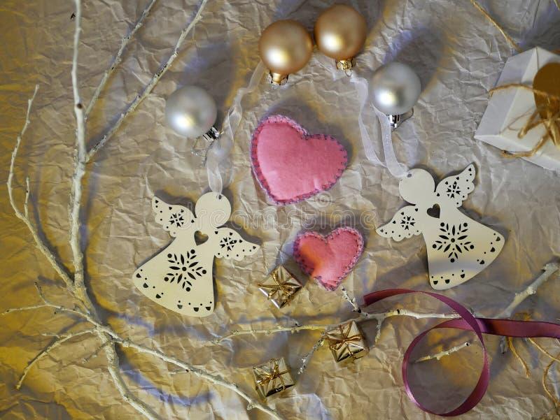 从一个对的装饰的季节性构成感觉的手工制造心脏,两白色天使圣诞装饰 免版税库存照片