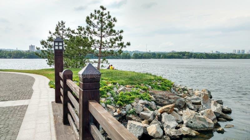 从一个小木桥的风景看法到一条宽河和一个小海岛有石岸的,整洁地被整理的草坪,松树 免版税库存图片